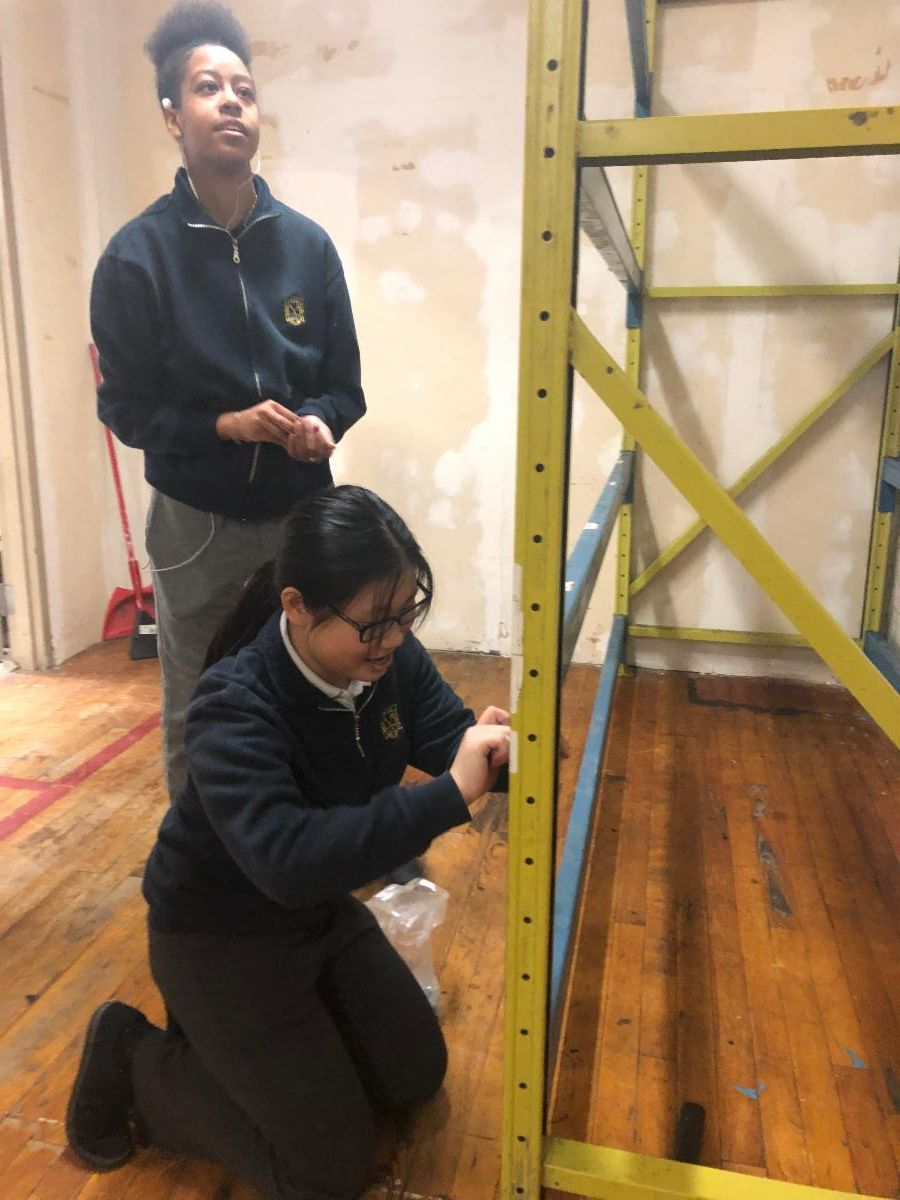 Two female student securing the shelving in the storage room.