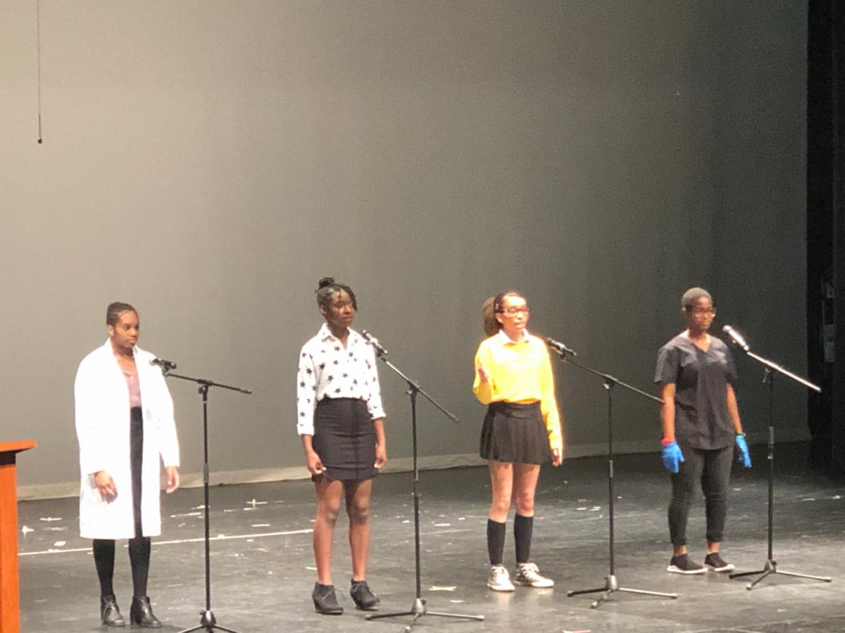 Four female students performing poetry on stage for Black History Month.
