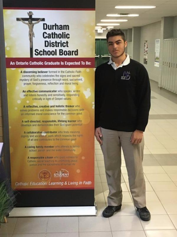 Male student standing beside Catholic Graduate Expectations banner
