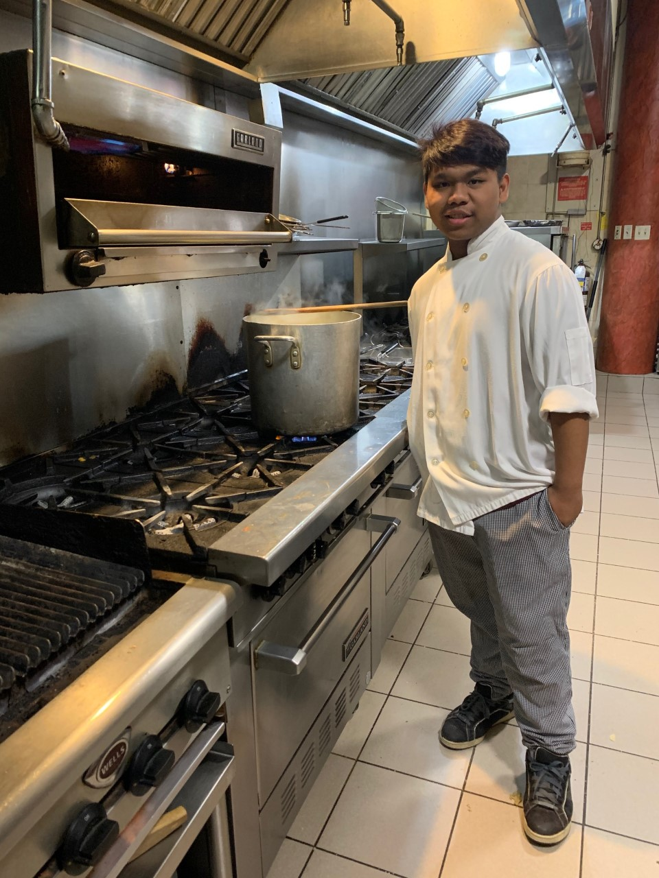 Male student standing beside an oven in a restaurant's kitchen