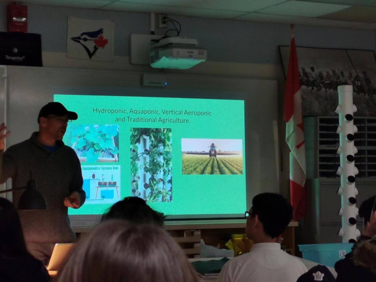 Male adult presenting to student on aeroponics gardening