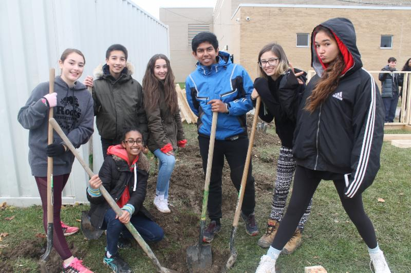 Female and male students working together to dig a whole to plant a fruit tree