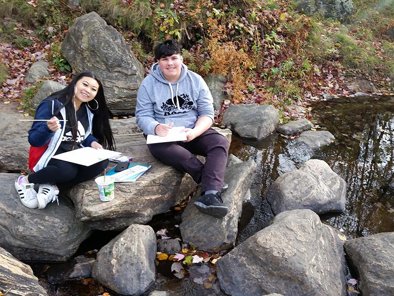 Female and male students sitting on rocks and painting nature.