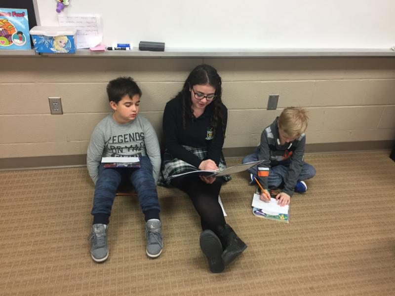 Female secondary student reading to elementary students on the carpet