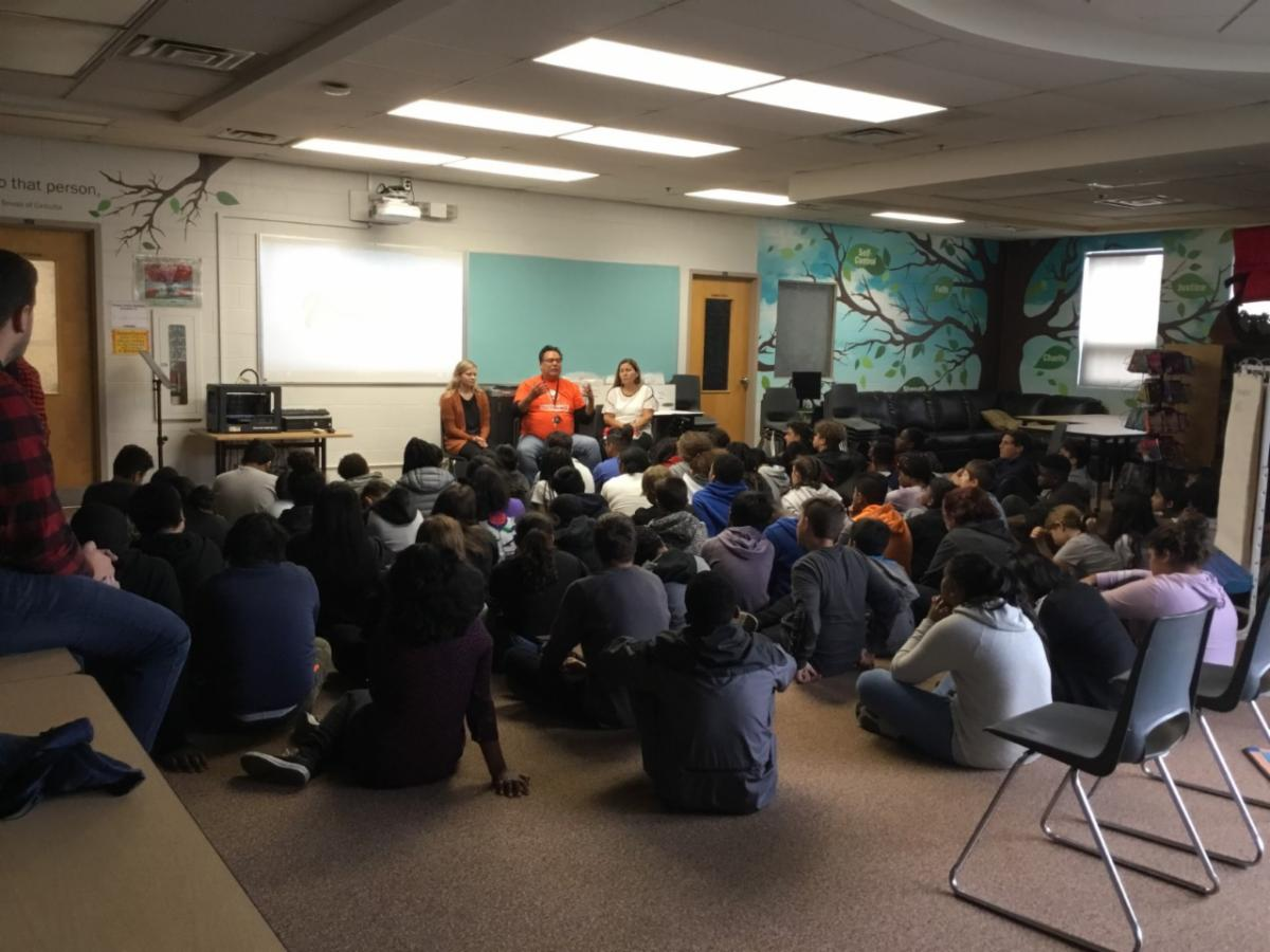 students sitting on a carpet listening to an Elder speak about Residential schools.