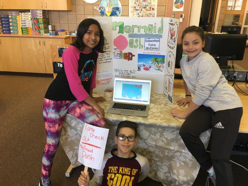 Two female and one male student standing by their invention display