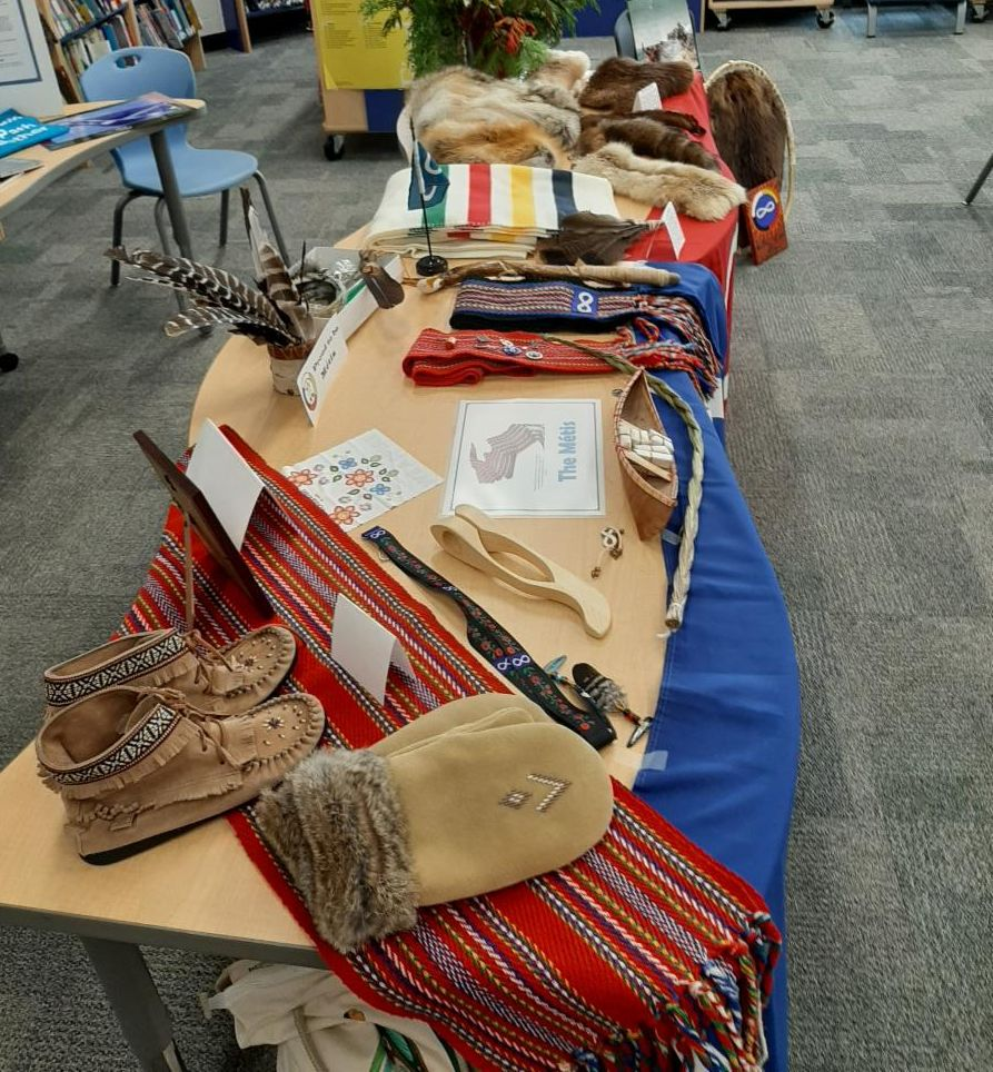 Table covered with Metis items such as furs, moccasins, Metis flags, Hudson Bay blanket, Metis sashes and birch bark canoes