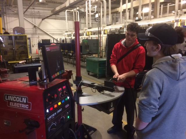 Two male students try welding at the college