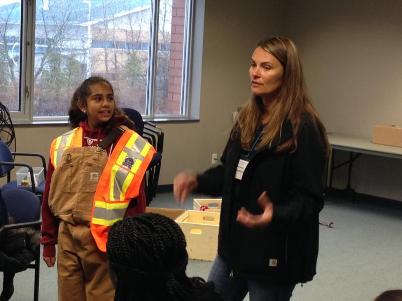 Female student wearing safety vest with female adult talking