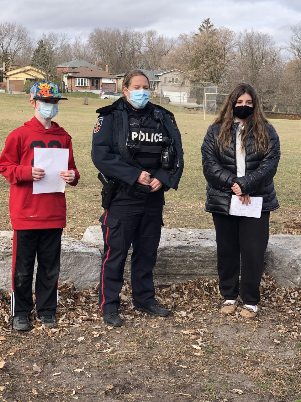 Two students standing beside a female police officer outside