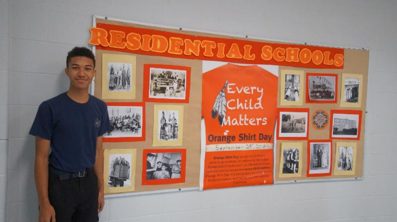 Male student standing beside the Orange Shirt Day/Residential School banner that he helped organize to promote Indigenous Education at his secondary school.