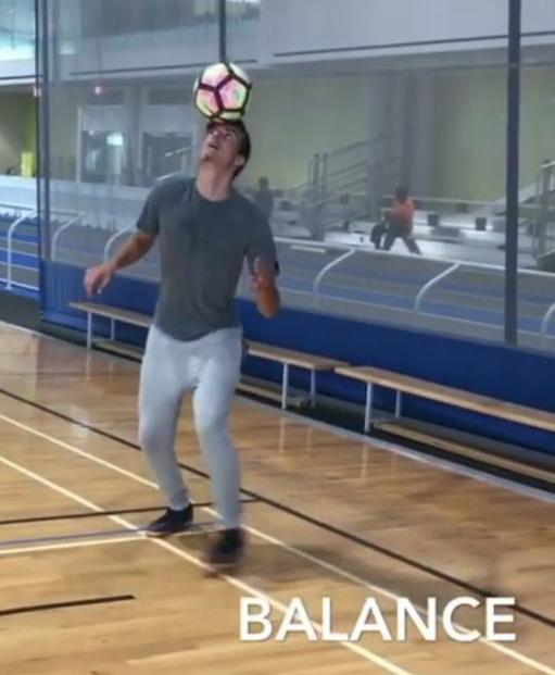 Male student balancing a ball on his head in a gym