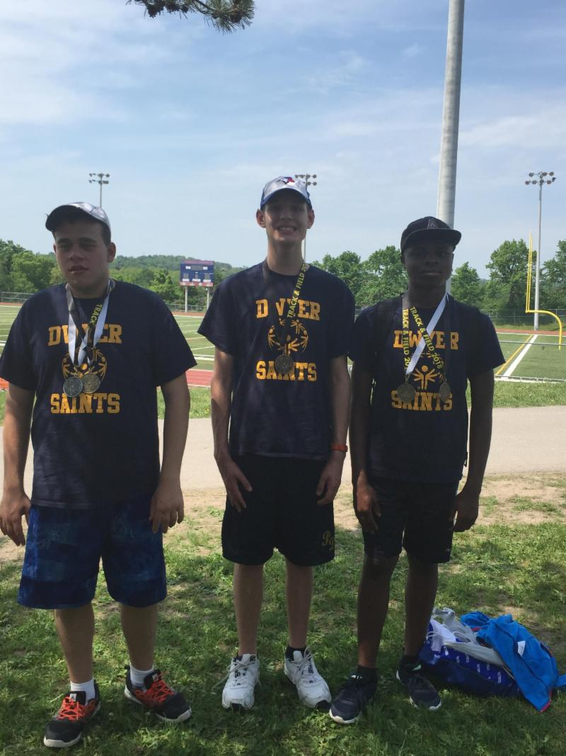 Three male students wearing Dwyer t-shirts with their medals