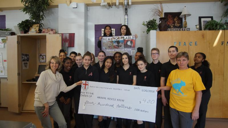 Teacher holding large cheque for $400.00 for Animal Rescue Krew with students in the background