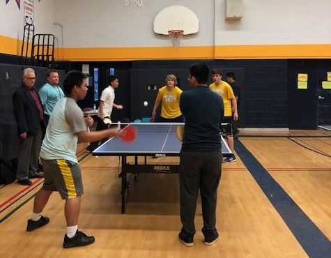 Four male students playing table tennis in the gym