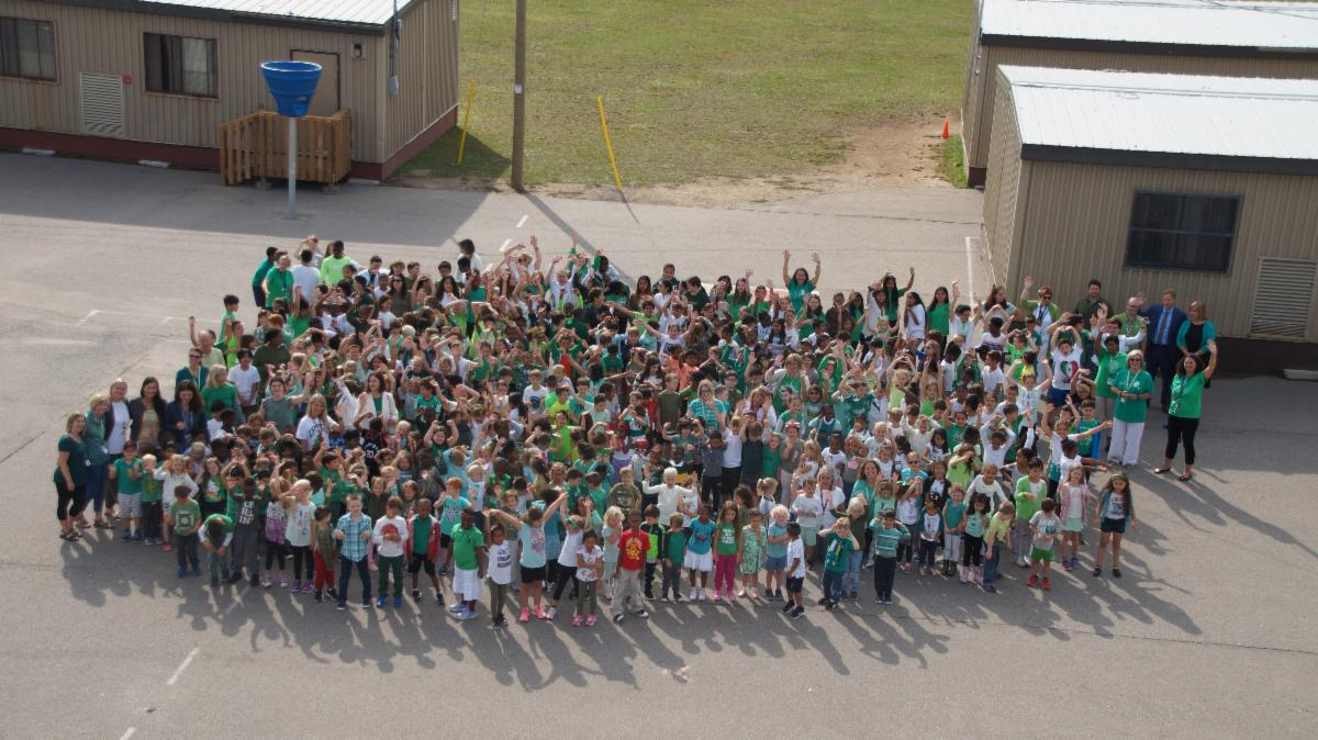 School community wearing white and green and waving