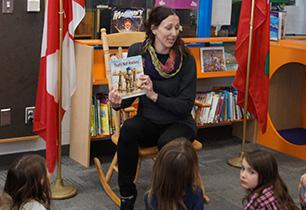 Female adult teacher reading a books to students in a library