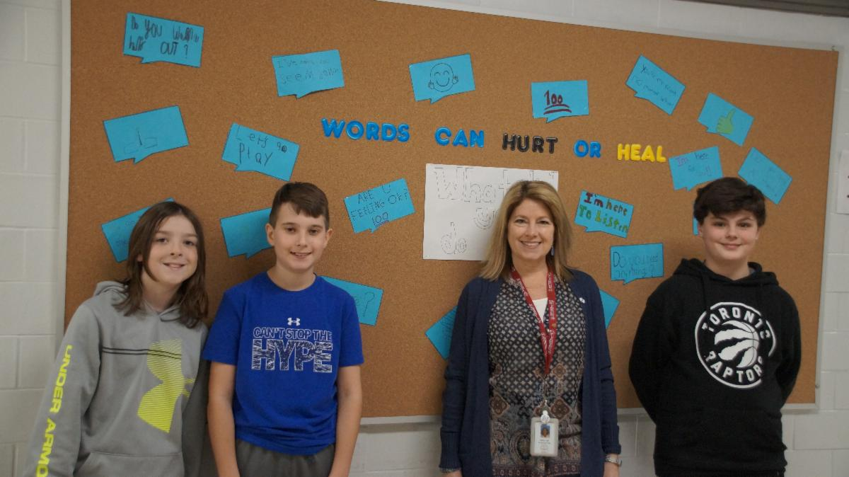 Three male students with female adult standing against bulletin board with words that can heal mental health