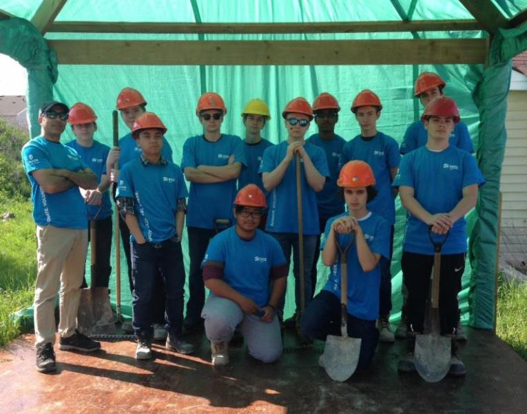 Male students wearing blue t-shirts and red hard hats standing outside in a sun shelter