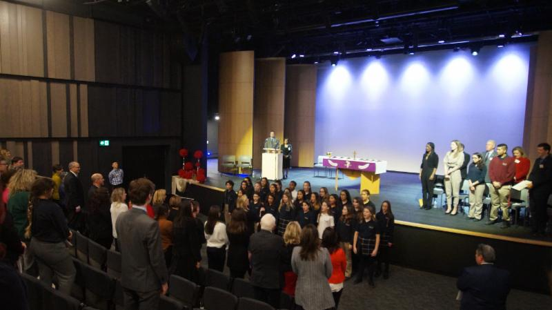 Vocal choir sing O'Canada in front of stage in theatre