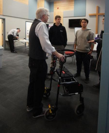 Male adult with walker brainstorms ideas with students for the umbrella holder for his walker