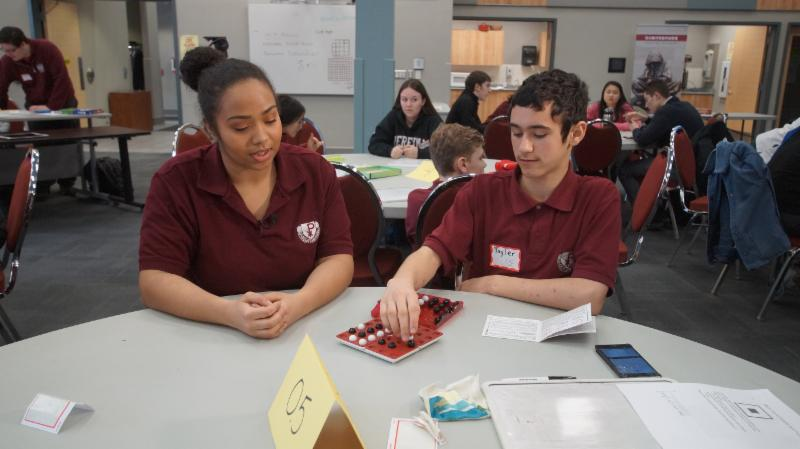 Female and male student playing a board game during a break