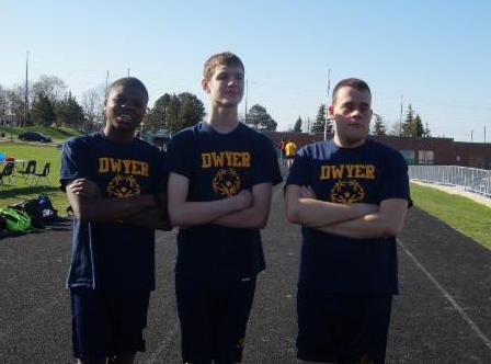 Three male students wearing Dwyer t-shirts and standing on the outside running track