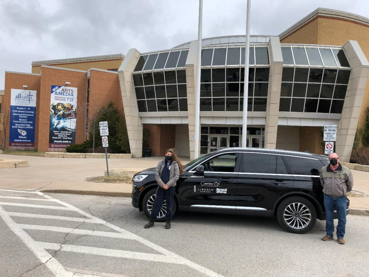 Lily and Peter with donated Ford vehicle outside of All Saints Catholic Secondary School