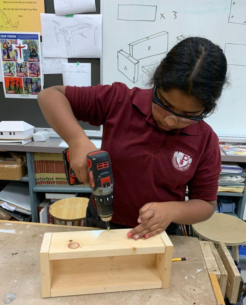 Female student drilling holes into her wood box.