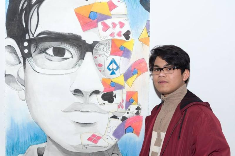 Male student standing beside a self drawing