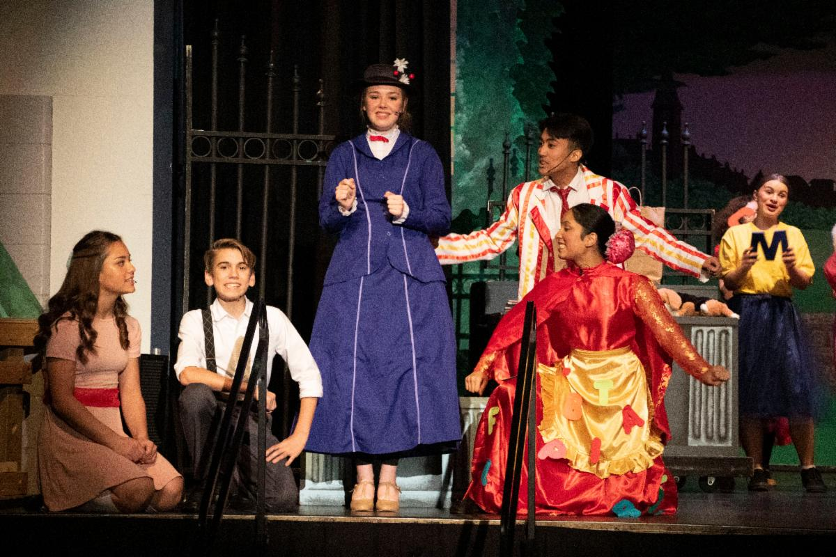 Female and male students on stage as they perform Mary Poppins