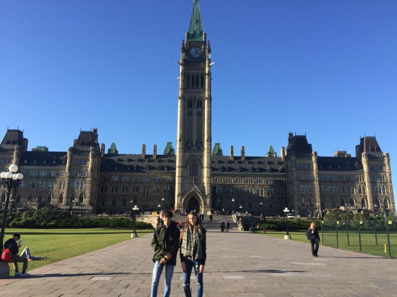 Male and female student standing in front of Parliament Building in Ottawa