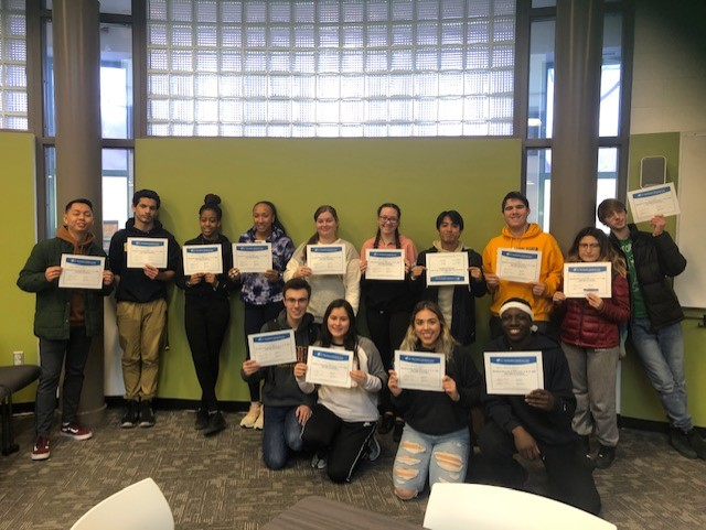 A group of male and female students holding their Level C First Aid and CPR training certificates
