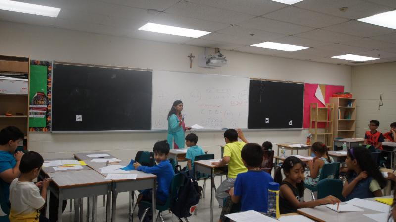 Female adults teaching elementary student another language in a classroom