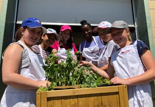 Six female students picking herbs and wearing aprons and hats