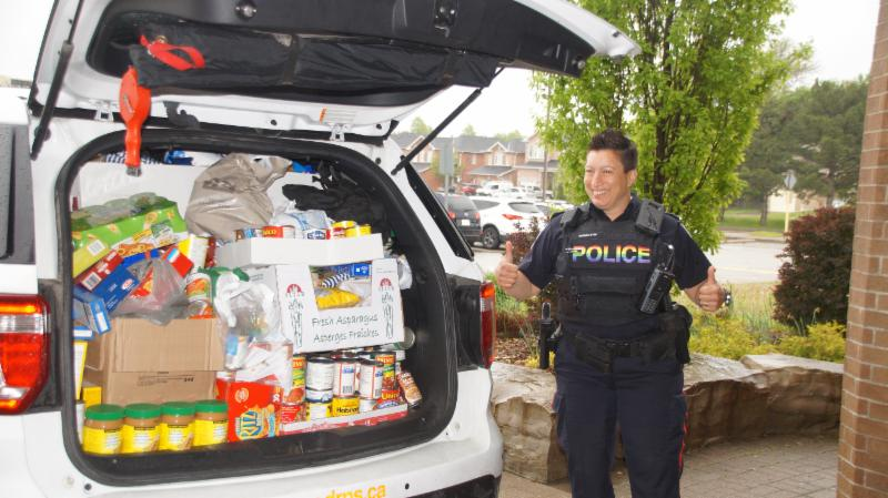 Female police offer gives a thumbs up to the students for all their work loading the cruiser and donating food.