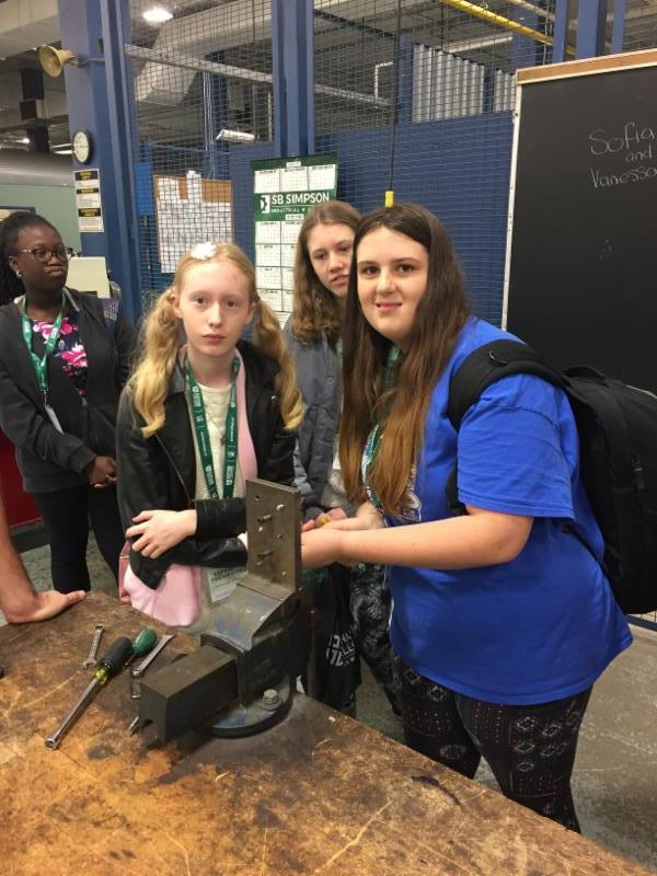 Three female students working with metal.