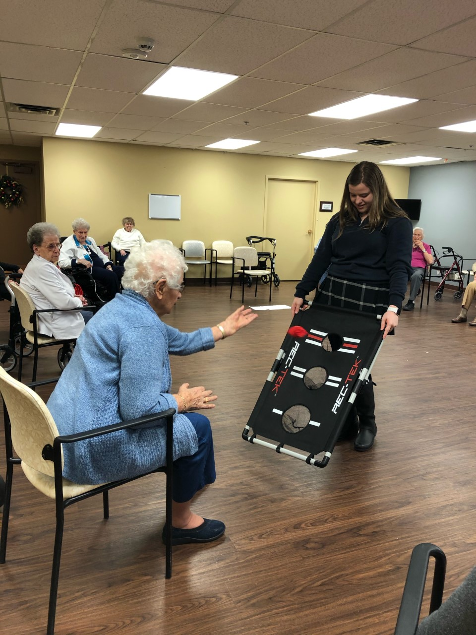 Female student working with elderly patients in a retirement home.