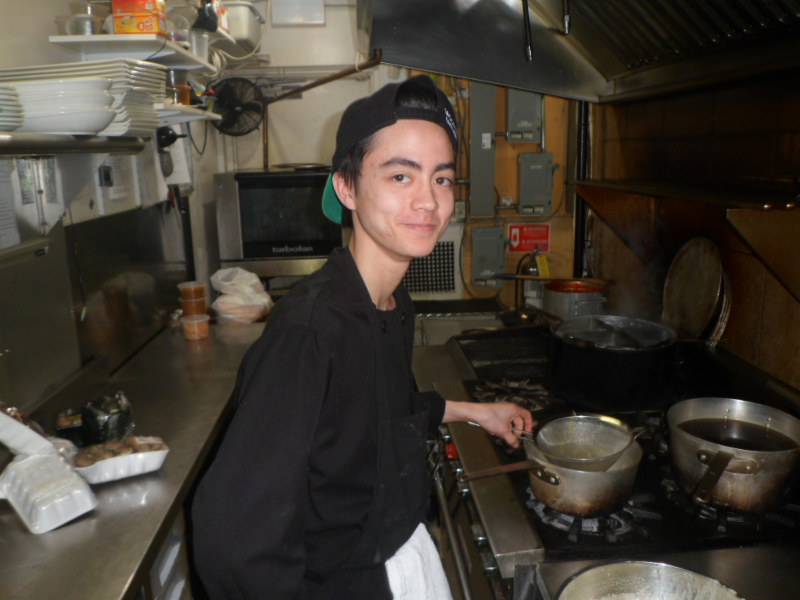 Male student cooking in kitchen.