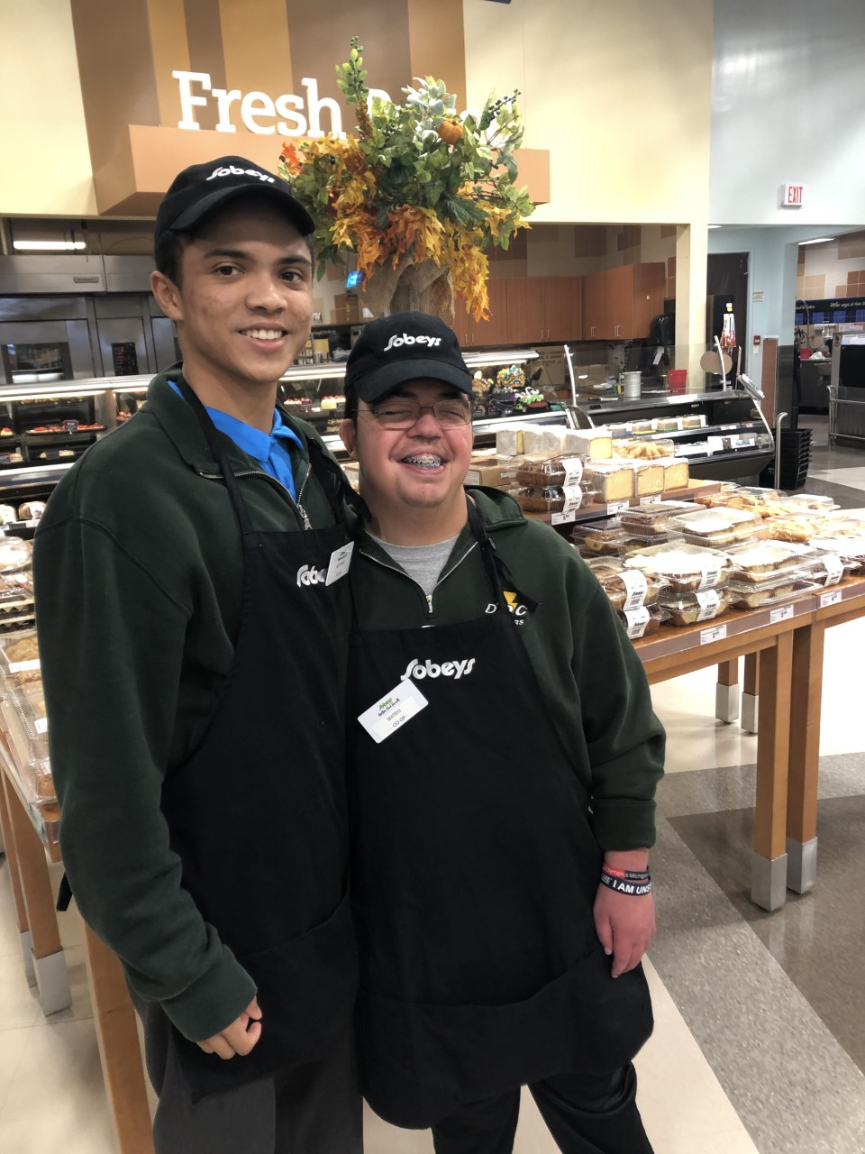 Two male students working in a bakery area of a grocery store