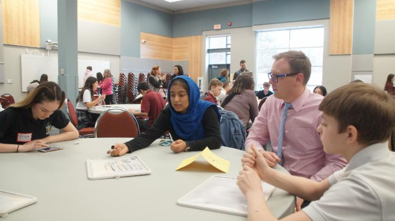 Female and male students sitting at a table working on Math questions