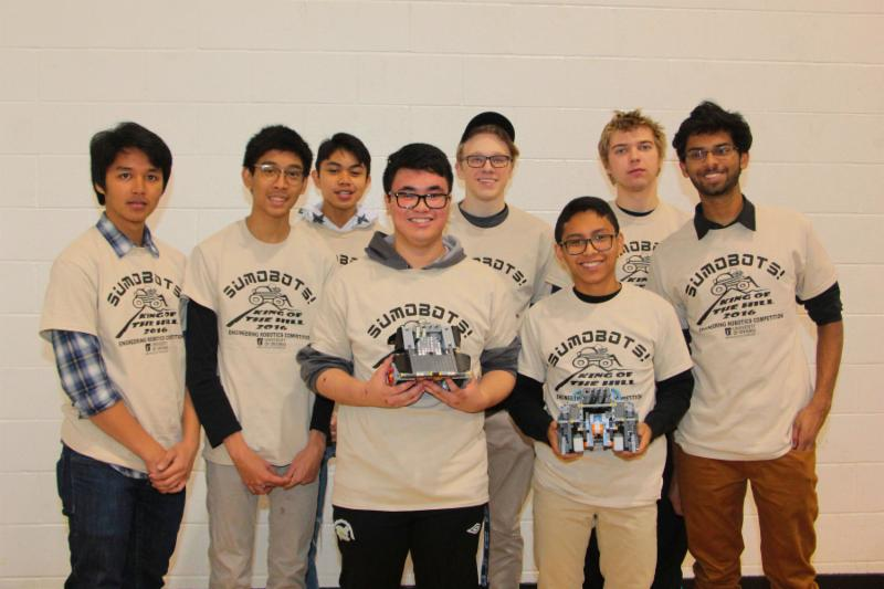 Eight male students wearing Sumobots t shirts and holding two robots
