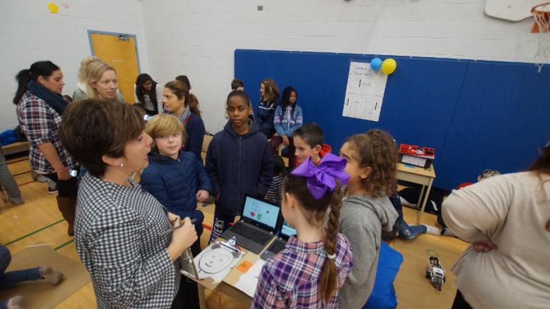 Students share information on their Robotics project with a female teacher