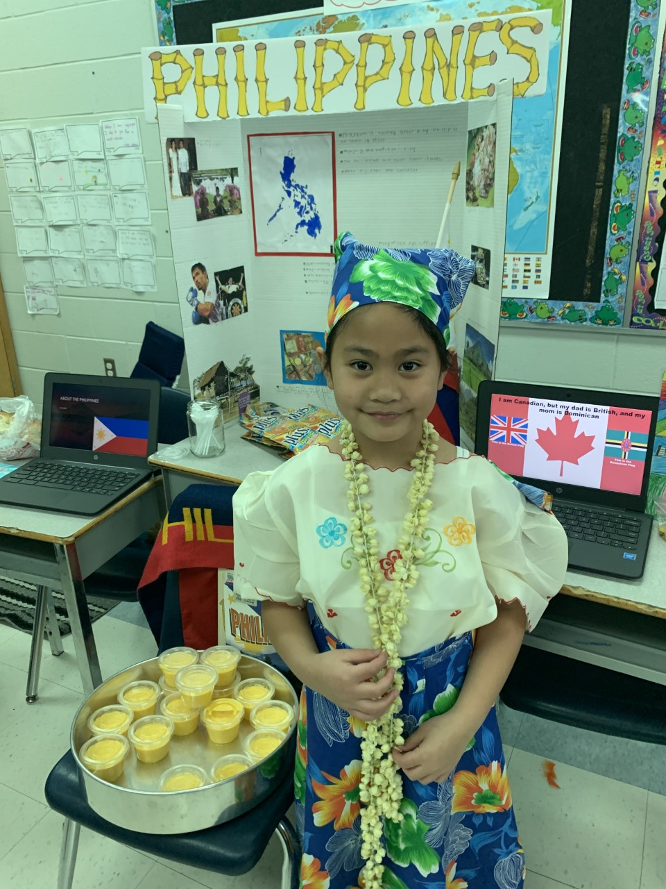 Female student dressed in traditional Philippines clothing and standing beside a desert with display in the background.