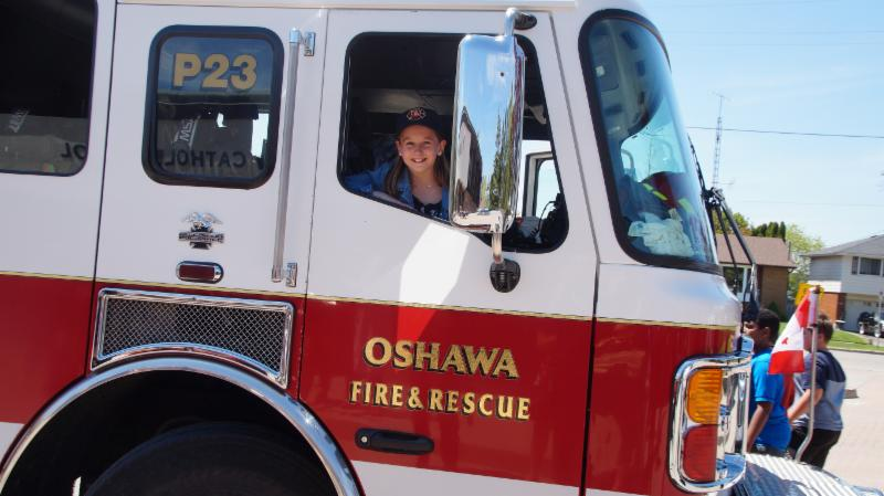 Female student named Junior Fire Chief sitting in the front seat of the truck