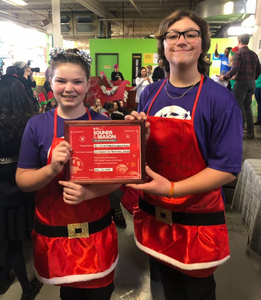 Two female students holding the Cooperation Award from the Daily Food Bank Sorting Challenge.