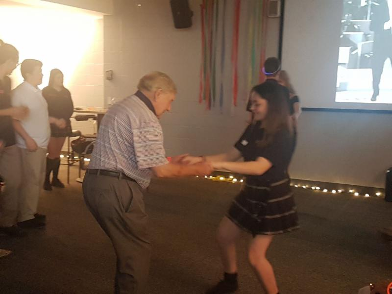 Female student dancing with a senior male adult at the school dance