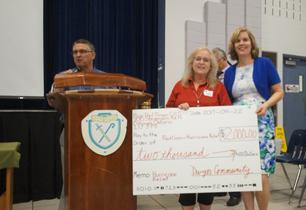Principal presents cheque to representative from the Red Cross