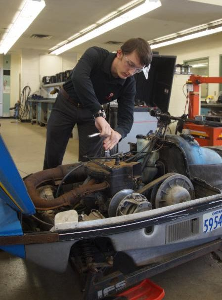 Male student working on a snowmobile in a school's autoshop