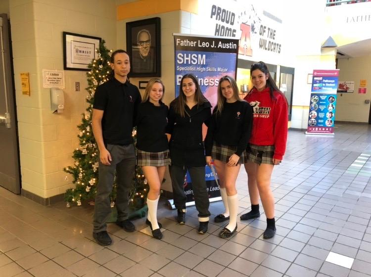 Students stand in front of Christmas tree in front lobby of  school